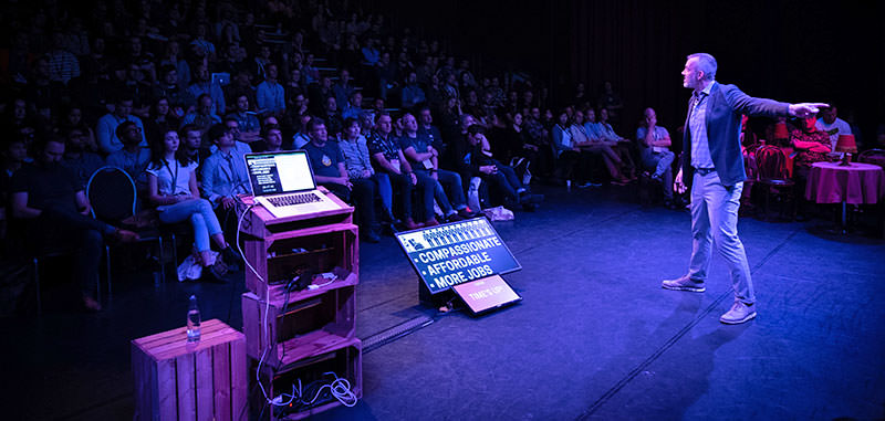 A photo showing Josh Clark opening the event in front of the audience