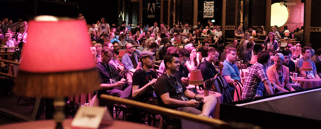 Photo showing the typical lamp of Düsseldorf's event and attendees sitting in the audience
