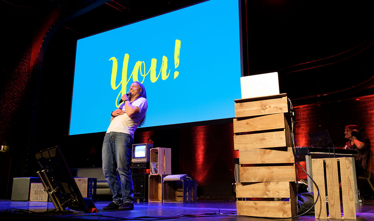 """Marc Thiele on stage with a slide saying """"you!"""""""