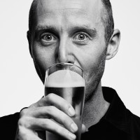 A photo with a portrait of Mike Hill drinking a beer